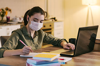woman working at home with medical mask on face. coronavirus qua